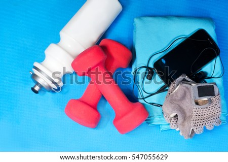 Sport items (bottle, dumbbells, towel, gloves ) on the sport mat