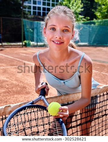 Sport kids girl with racket and ball looking at camera on  brown tennis court. - stock photo