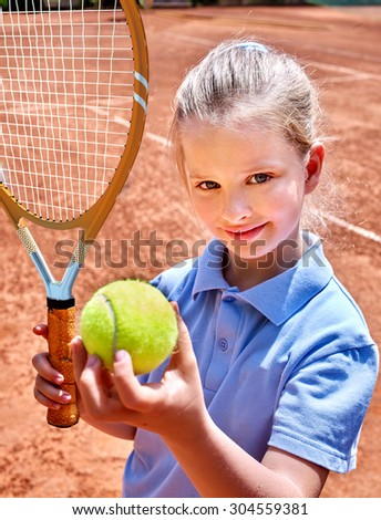 Sport kids girl with racket and ball on  brown  court. Child tennis player. - stock photo