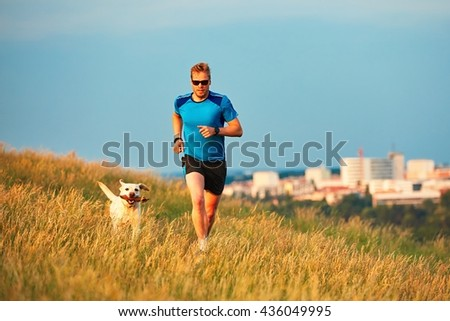 Sport lifestyle with dog. Athletic young man and labrador retriever are running on the hillside outside the city. Prague, Czech Republic. - stock photo