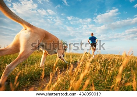 Sport lifestyle with dog. Athletic young man and labrador retriever are running on the hillside outside the city.