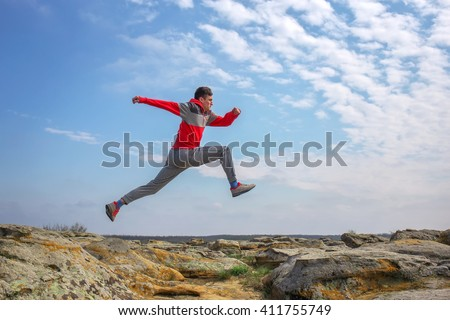 Sport man running, jumping over rocks in mountain area. Fit male runner exercise training and jumping outdoors in beautiful nature
