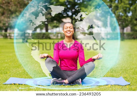 sport, meditation, park and lifestyle concept - smiling woman meditating on mat outdoors - stock photo