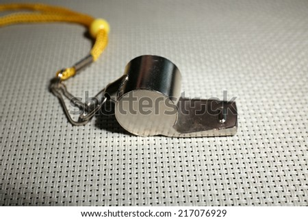Sport metal whistle on light background - stock photo