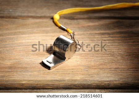 Sport metal whistle on wooden background - stock photo