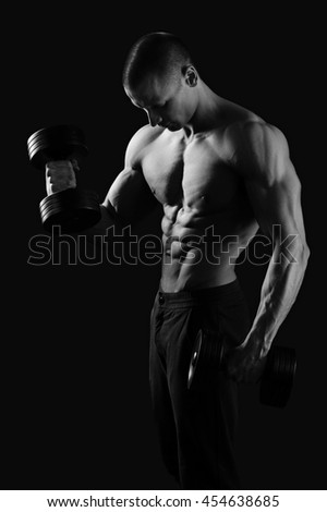 Sport mood. Monochrome shot of a ripped and tones fitness man working out with weights - stock photo