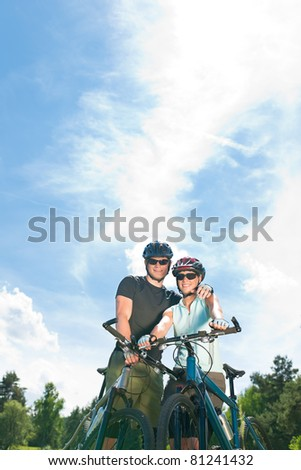 Sport mountain biking happy couple relax in meadows sunny countryside - stock photo