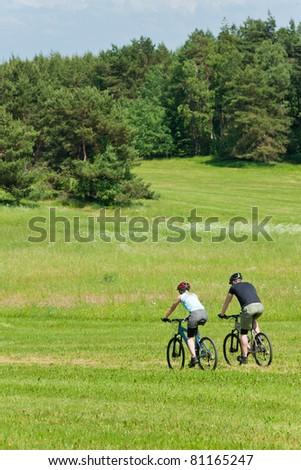 Sport mountain biking happy couple riding downhill in sunny countryside - stock photo