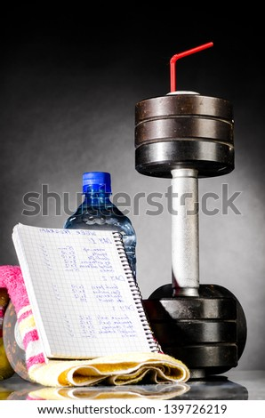 sport nutrition. metal barbells with red straw - stock photo