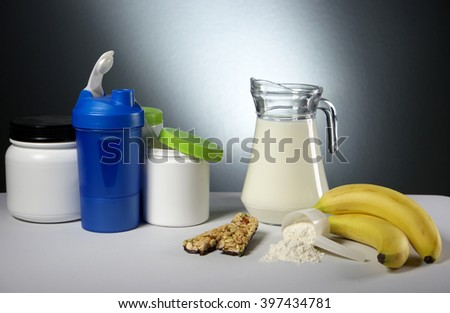 Sport Nutrition Supplement containers with jug of milk - stock photo