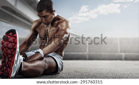 Sport. Runner. Muscular young african man looking away with stretching his leg.