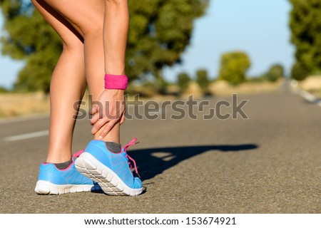 Sport running ankle sprain. Sportswoman touching painful twisted or broken ankle. Athlete runner training accident. - stock photo