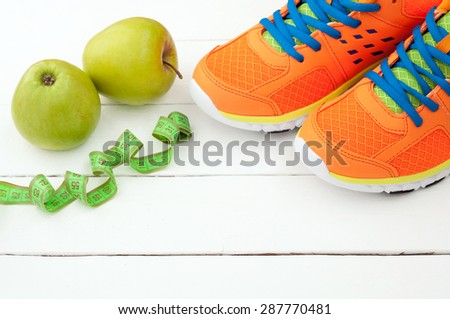 Sport shoes and apple on white wooden background. Sport equipment. Tools for sport and diet. Selective focus - stock photo