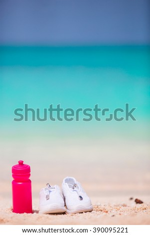 Sport shoes and bottle on white sandy beach - stock photo