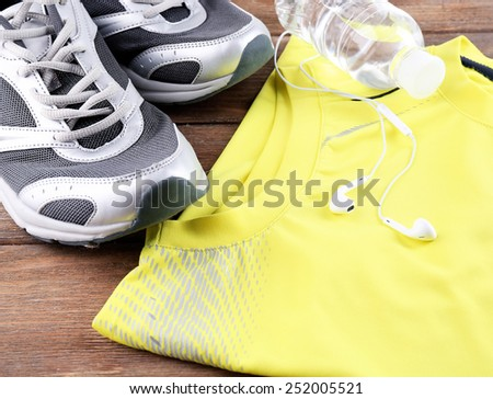 Sport shoes and clothes on wooden background - stock photo