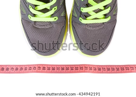 Sport shoes and pink measure tape  isolated on white background.Sport shoes and centimeter as a fitness running - stock photo