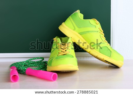 Sport shoes and skipping rope on blackboard background - stock photo