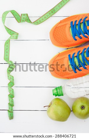 Sport shoes, apple and bottle of water on white wooden background. Sport equipment. Selective focus. Top view - stock photo
