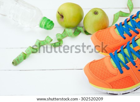 Sport shoes, apple and bottle of water on white wooden background. Sport equipment. Selective focus - stock photo