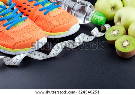 Sport shoes, fruits,  bottle of water and measuring tape on dark background. Sport equipment. Concept healthy life, sports and diet. Selective focus - stock photo