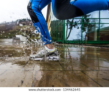 Sport shoes making big water splash running