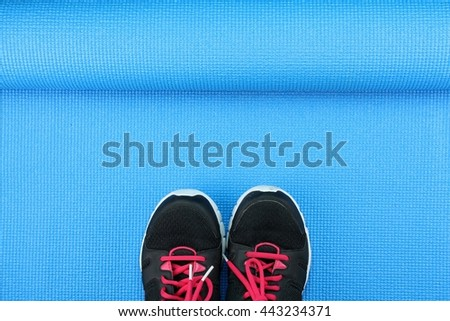 Sport shoes on blue yoga mat background, Fitness accessories and exercise Equipment, No gym workout concept. - stock photo