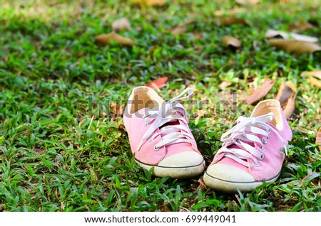 Sport shoes, Pink sneakers on grass,Sports equipment on green grass background.