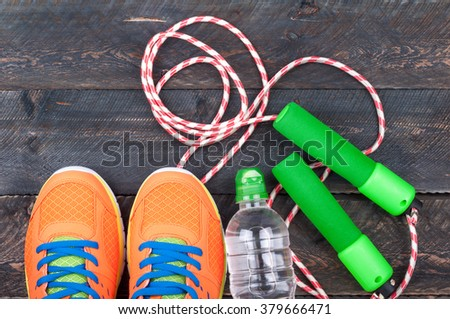 Sport shoes, skipping rope and bottle of water on the old wooden background. Sports equipment. Sport and healthy life concept. Top view - stock photo