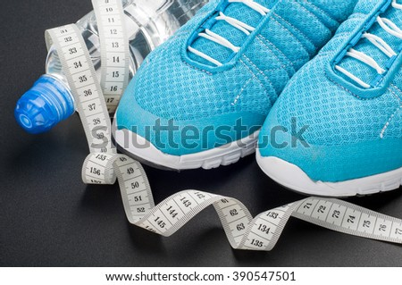 Sport shoes, water and measuring tape on dark background. Sport equipment. Concept healthy, active and sports life. Selective focus - stock photo