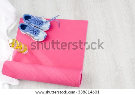 Sport shoes, yoga mat, bottle of water and centimeter on wooden background. Sport equipment. Concept healthy life. Selective focus - stock photo