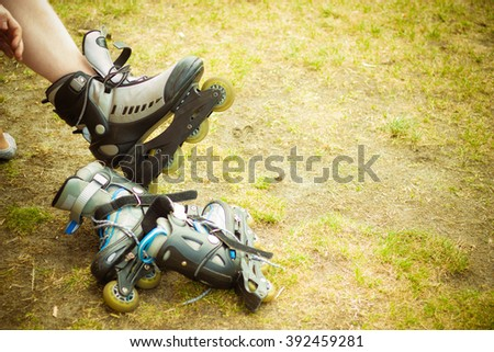 Sport skating in park. Guy putting on roller skates. Man in outdoor fitness activities.  - stock photo