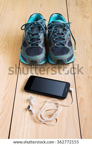 Sport sneakers and smartphone with headphones on wooden background