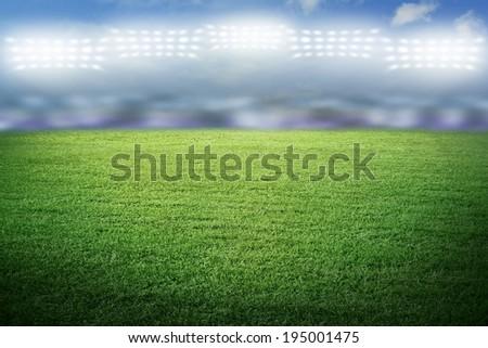 Sport stadium in spotlight with green grass field - stock photo
