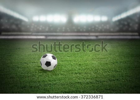 Sport stadium with football ball on grass field - stock photo