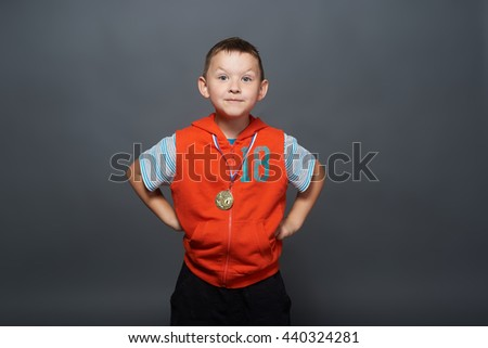 Sport success and win concept - smiling athlete champion child boy hand with first place victory gold medal award