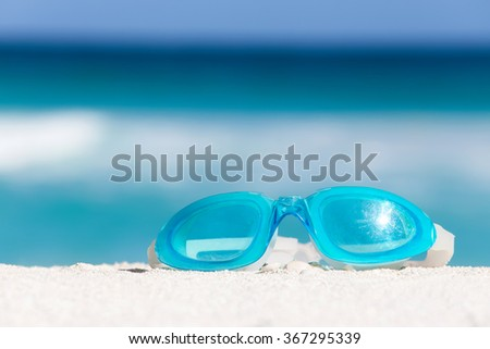 Sport swimming glasses on white sand against turquoise caribbean sea water. Tropical summer vacation concept - stock photo