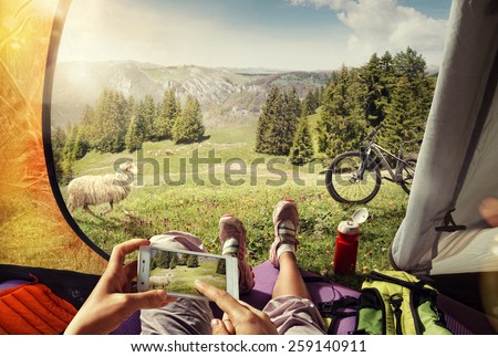 Sport. Tourism. Traveling. Cyclist in the tent with the mobile - stock photo
