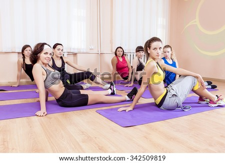 Sport, Training anf Healthy Lifestyle Concepts. Group of Seven Caucasian Women Sitting on Floor Mats During Gym Fitness Class. Horizontal Image Orientation - stock photo