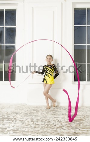 Sport training beautiful girl with Pink Rhythmic gymnastics ribbon in white room jumping and doing professional exercises  - stock photo