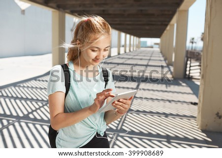 Sport, training, technology, fitness and lifestyle concept. Young asian woman wearing sports wear looking at mobile phone. Female athlete listening music with cell phone.  - stock photo