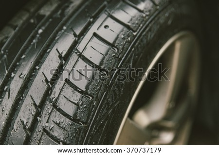 Sport tyre close up. close up on rain drops on a car tyre. concept about transportation - stock photo