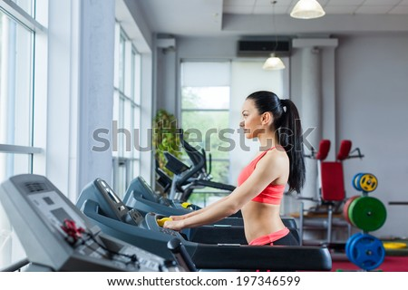 sport woman at the gym run exercising. walk on cardio machine, fitness center - stock photo