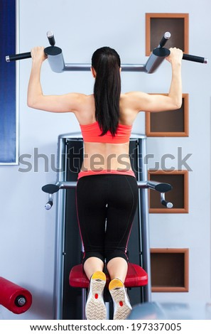 Sport woman doing exercises back arm muscle on power training apparatus in the gym. Pulling up on the horizontal bar, girl exercises working out machine in fitness center   - stock photo