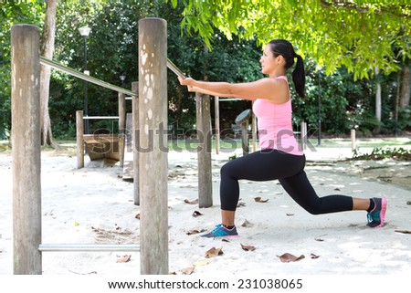 Sport woman doing lunges by the exercise bar in outdoor park - stock photo