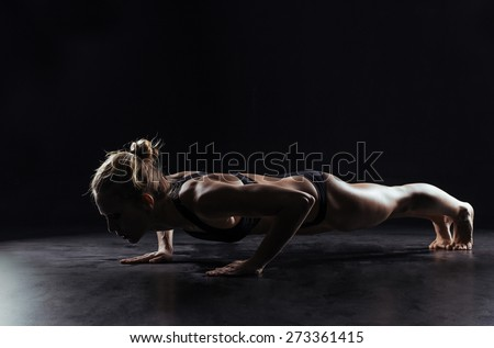 Sport woman doing push-ups on black background - stock photo