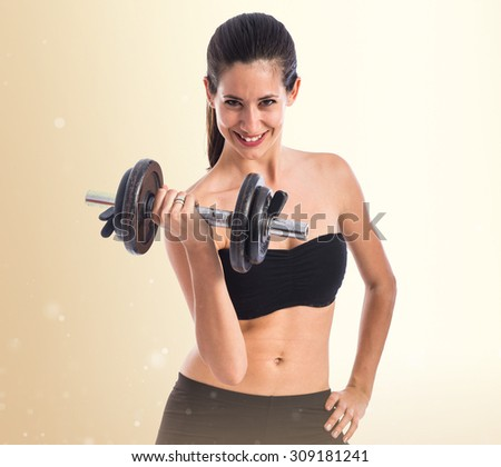 Sport woman doing weightlifting over ocher background