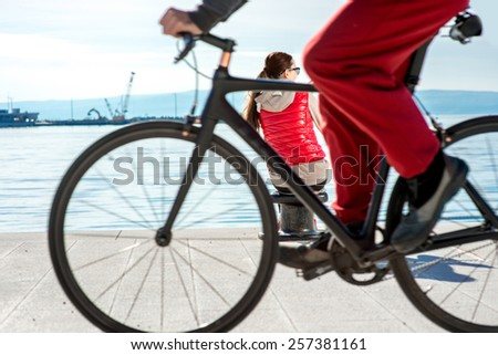 Sport woman dressed in warm clothes resting with phone and headphones after the excercise on the promenade on the spring - stock photo