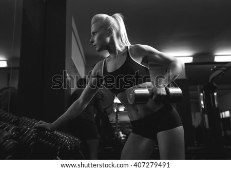 Sport woman. Fitness training with dumbbells. Woman in sport wear with perfect fitness body in gym. Woman during physical exercise with dumbbells. Black and white image. advertising banner. - stock photo