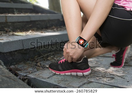 Sport woman hand tying shoelaces wearing touchscreen smartwatch with health sensor app icon on forest trail background - stock photo