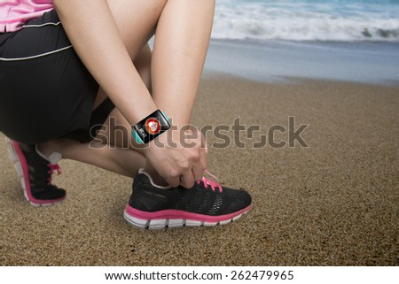 Sport woman hand tying shoelaces wearing touchscreen smartwatch with health sensor app icon on natural sea beach background - stock photo